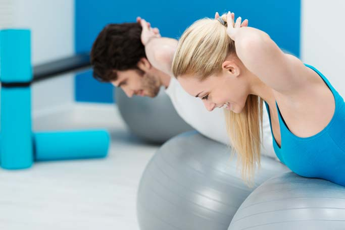 Healthy young couple doing Pilates exercises together in the gym shaping and toning their muscles while doing balancing exercises on gym balls